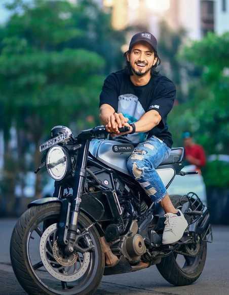 Faisal Shaikh posing on a bike on Instagram